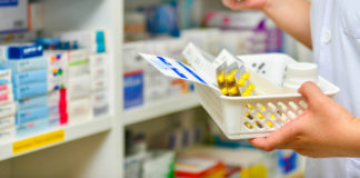 A hand holding a basket with various leaflets and boxes of pills.