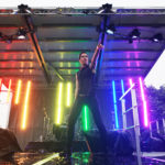 Brie Treviranus striking a pose on stage with the stage lights set to the pride rainbow.