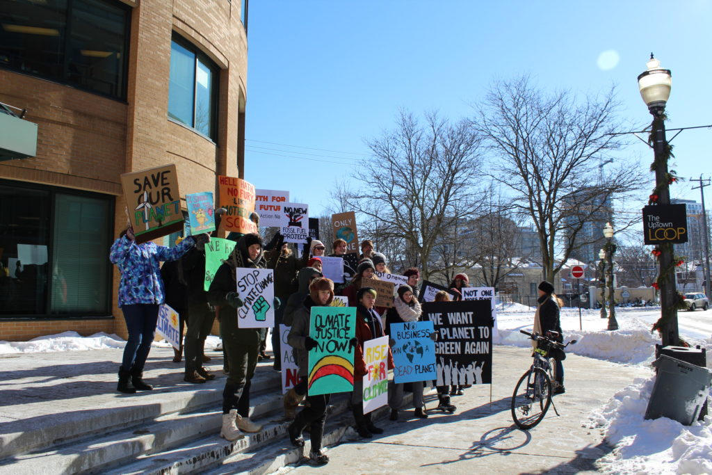 Protestors stand on the stairs in front of Waterloo City Hall holding signs demanding climate action.